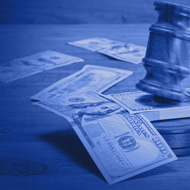 Gavel laying on a bundle of money on a table